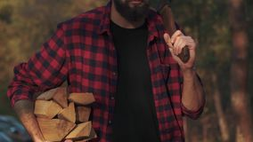 Bearded guy walk in the forest with chopped logs in one hand and axe in his shoulder. Forester carries firewood.
