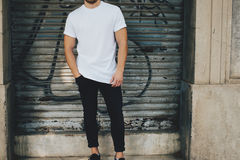 Bearded guy wearing white blank t-shirt and black jeans, standing opposite garage Royalty Free Stock Images