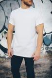 Bearded guy wearing white blank t-shirt and black jeans, standing opposite garage. Vertical Stock Image
