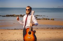 Bearded guy in white shirt pose with guitar Royalty Free Stock Photos