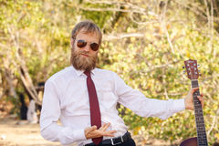 Bearded guy in white shirt pose with guitar Royalty Free Stock Photography