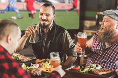 Bearded guys relaxing with beer in sports bar stock photography