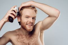 Bearded hairy man sprinkles lotion on hair. royalty free stock photos
