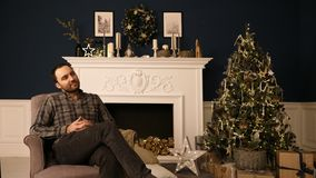 Bearded handsome hipster young man in Christmas roomthinking of gift ideas. Daydreaming. stock photography