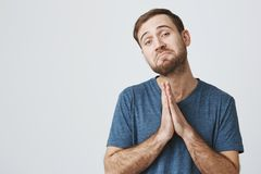 Bearded handsome male wears casual clothes keeps palms together as prays for good luck, has displeased unhappy stock photo