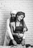 Baker cooking cakes with girl. Bearded handsome man, baker or cook cooking sweet cakes to winking, pretty girl or beautiful women in red apron messy with flour Stock Image