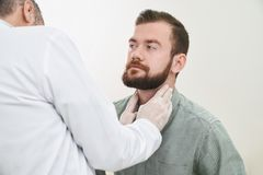 Bearded handsome man having neck and lymph nodes checked. stock images