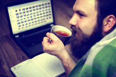 Bearded handsome man lies on the floor wrapped in a plaid, and working laptop Royalty Free Stock Photography