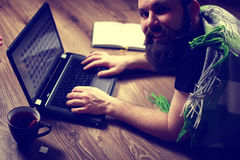 Bearded handsome man lies on the floor wrapped in a plaid, and working laptop Stock Photography
