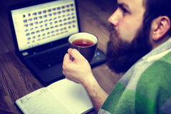Bearded handsome man lies on the floor wrapped in a plaid, and working laptop Royalty Free Stock Photos