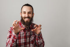 Bearded handsome man scares in red squared shirt on grey backgro Stock Photography
