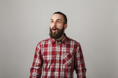 Bearded handsome man scares in red squared shirt on grey backgro Royalty Free Stock Image