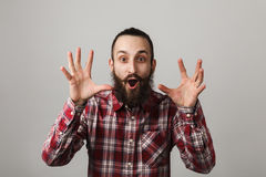 Bearded handsome man scares in red squared shirt on grey backgro Royalty Free Stock Photos