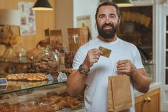 Bearded handsome man shopping at the local bakery royalty free stock photos