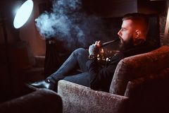Bearded handsome man is sitting near fireplace and smoking hookah, making good misty vapour.  stock photo