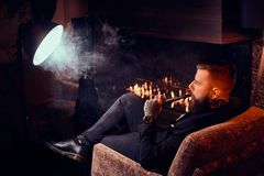 Bearded handsome man is sitting near fireplace and smoking hookah, making good misty vapour.  stock photography