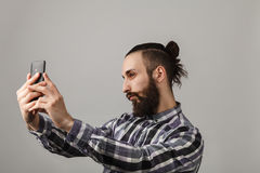 Bearded handsome man is taking selfie by phone in blue squared s Stock Photography