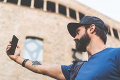Bearded handsome man wearing black snapback cap and making selfie with his own smartphone. Man walking on street and royalty free stock image