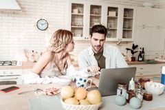 Bearded handsome positive man in a white shirt showing pictures on a laptop to his wife. Pictures. Bearded handsome positive men wearing a white shirt showing stock image