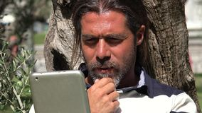 Male Using Tablet. A bearded handsome Spanish male Stock Photo