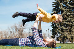 Bearded happy father having fun outdoors with his little son. Picture of bearded happy father having fun outdoors with his little son in the park. Looking aside Royalty Free Stock Photography