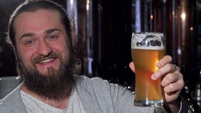 Bearded happy man smiling, holding up his beer glass to the camera. Cheerful man enjoying delicious craft beer at the pub, celebrating with a toast. Festivity royalty free stock photos