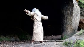 Bearded hermit in a cave is praying. Old monk live in forest stock footage