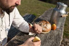 Bearded hermit eating cheese and bread in the nature Stock Images