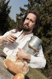 Bearded hermit eating cheese and bread in the nature Stock Image