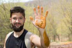 Bearded hiker with his hand in mud Stock Photography