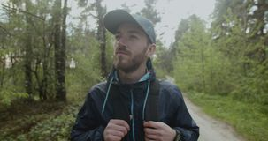 Bearded Hiking Man. Bearded man dressed in cap and backpack walking in the forest stock footage