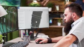 Bearded hipster architect works on 3D model of a turbine. In the background - modern creative media house stock footage