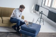 Bearded hipster boy professional freelance social media content writer keyboarding on laptop computer while sitting in coworking royalty free stock photography