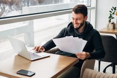 Bearded hipster at a cafe with the papers and laughs. Male freelancer connecting to wireless via laptop computer, thoughtful businessman work on notebook while Royalty Free Stock Images