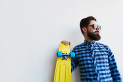 Bearded hipster in checkered shirt holding yellow skateboard Stock Image