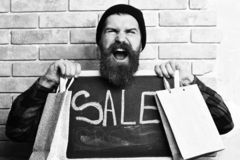 Bearded hipster holding shopping packages and board with Sale inscription. Bearded man, long beard. Brutal caucasian happy hipster with moustache holding royalty free stock photos