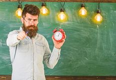 Bearded hipster holds clock, chalkboard on background, copy space. Man with beard and mustache on strict face. Teacher. In eyeglasses holds alarm clock and stock photo