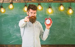 Bearded hipster holds clock, chalkboard on background, copy space.. Teacher in eyeglasses holds alarm clock and pointing stock image
