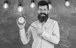 Bearded hipster holds clock, chalkboard on background. Man with beard and mustache on smiling face stands in classroom stock photos