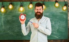 Bearded hipster holds clock, chalkboard on background. . Teacher in eyeglasses holds alarm clock and pen. Discipline stock photo
