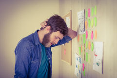 Bearded hipster looking at brainstorm wall Stock Photography