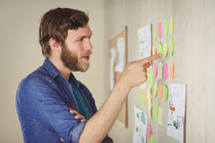 Bearded hipster looking at brainstorm wall Royalty Free Stock Photos
