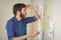 Bearded hipster looking at brainstorm wall Stock Photos