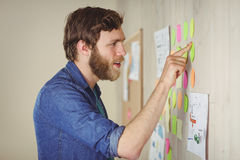 Bearded hipster looking at brainstorm wall Stock Images