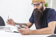 Bearded hipster is looking at his mobile. Close up of hipster with long beard looking at his smartphone screen and holding a pen in his hand royalty free stock photo