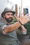 Bearded hipster making selfie via smartphone on terrace of cafe. Positive man relaxing out side. Bearded hipster making selfie via smartphone on terrace of cafe Royalty Free Stock Photography