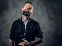 Bearded hipster male in a black shirt. Stylish tattooed, bearded hipster male in a black shirt posing on grey background Royalty Free Stock Images