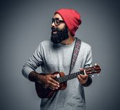 Bearded hipster male in red hat playing on ukulele. royalty free stock photos