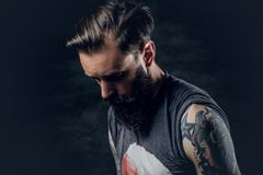 Bearded hipster male with tattoos on arms. Bearded hipster male with tattoos on arms, looking down Royalty Free Stock Image