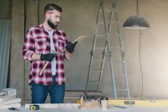 Bearded hipster man is carpenter, builder, designer stands in wo. Rkshop,holds clipboard and hammer, reads instruction.On desk construction tools,in background stock photos
